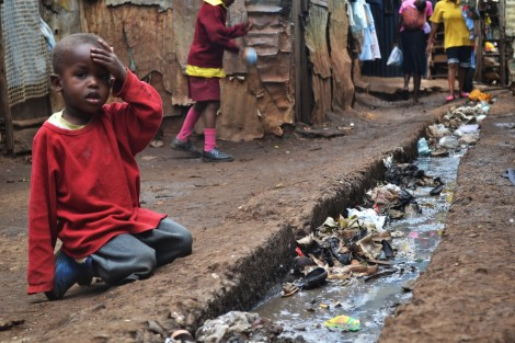 A young boy sits over an open sewer in the Kibera slum, Nairobi.